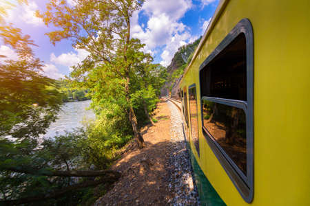 Train ride, view from a window. Old train passing green vegetation. View from the window. Traveling by train to sunset. Sunset scenery and a train gilded by sun, view from a train window. Czechia.