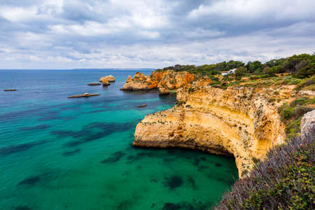View of stunning beach with golden color rocks in Alvor town , Algarve, Portugal. View of cliff rocks on Alvor beach, Algarve region, Portugal. Standard-Bild - 131686115