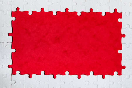Framing in the form of a rectangle, made of a white jigsaw puzzle. Frame text and jigsaw puzzles. Frame made of jigsaw puzzle pieces on red background. Banco de Imagens