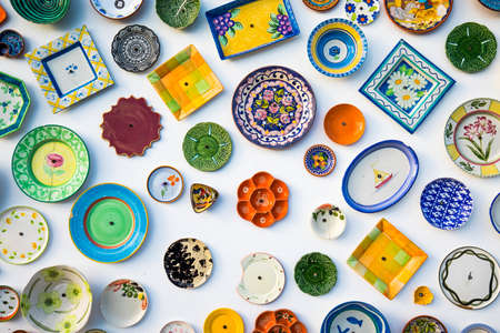 Sammlung farbenfroher portugiesischer Keramik, lokale Handwerksprodukte aus Portugal. Keramikplatten werden in Portugal ausgestellt. Bunt von Vintage-Keramikplatten in Sagres, Portugal.