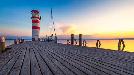 Lighthouse at Lake Neusiedl, Podersdorf am See, Burgenland, Austria. Lighthouse at sunset in Austria. Wooden pier with lighthouse in Podersdorf on lake Neusiedl in Austria. 스톡 콘텐츠