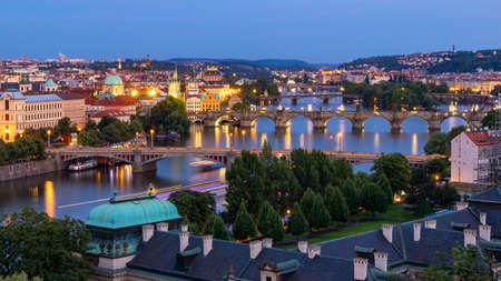 Prague, Czech Republic bridges panorama with historic Charles Bridge and Vltava river at night. Pargue at dusk, view of the Lesser Bridge Tower of Charles Bridge (Karluv Most). Czechia.