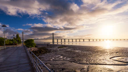 Vasco da Gama bridge at sunrise in Lisbon, Portugal. Vasco da Gama Bridge is a cable-stayed bridge flanked by viaducts and rangeviews that spans the Tagus River in Parque das Nações in Lisbon.