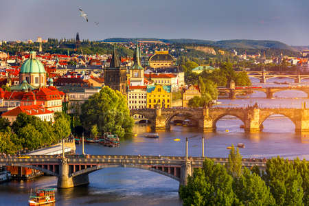 Old Town pier architecture and Charles Bridge over Vltava river in Prague with seagulls, Czech Republic. Prague iconic Charles Bridge (Karluv Most) and Old Town Bridge Tower at sunset, Czechia.
