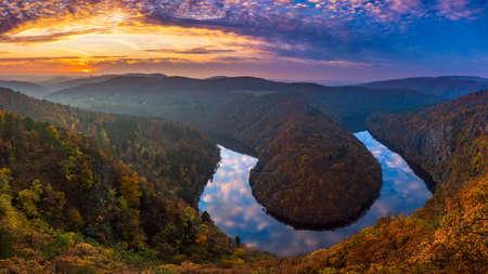Canyon del fiume con acqua scura e foresta colorata d'autunno. Curva a ferro di cavallo, fiume Moldava, Repubblica Ceca. Bellissimo paesaggio con fiume Archivio Fotografico