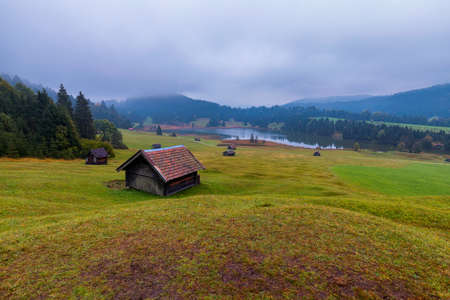 Panoramic morning scene of Wagenbruchsee (Geroldsee) lake with Zugspitze mountain range on background. Amazing autumn view of Bavarian Alps, Germany, Europe. Wooden hut on meadow by Geroldsee lake. Standard-Bild