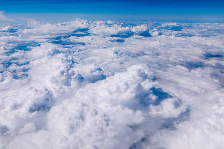 Amazing clouds and the sky as seen through the window of an aircraft. Clouds, sun, sky as seen through window of an aircraft. Bright blue sky with clouds and sunlight seen through an airplane window. Banque d'images - 137152990