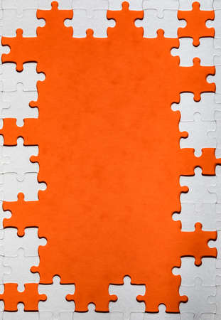 Framing in the form of a rectangle, made of a white jigsaw puzzle. Frame text and jigsaw puzzles. Frame made of jigsaw puzzle pieces on orange background. Stock fotó