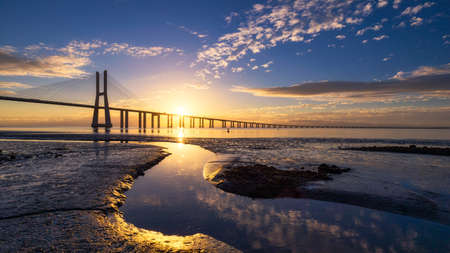 Vasco da Gama bridge at sunrise in Lisbon, Portugal. Vasco da Gama Bridge is a cable-stayed bridge flanked by viaducts and rangeviews that spans the Tagus River in Parque das Nações in Lisbon. Standard-Bild - 137153143