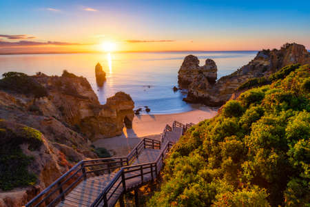 Sunrise at Camilo beach in Lagos, Algarve, Portugal. Wooden footbridge to the beach Praia do Camilo, Portugal. Picturesque view of Praia do Camilo beach in Lagos, Algarve region, Portugal. Standard-Bild - 137153172