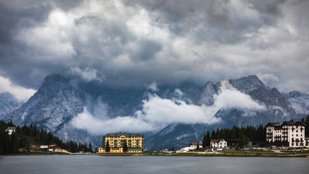 Misurina Lake in the Dolomites mountains in Italy near Auronzo di Cadore on a cloudy day, Sorapiss mountain in the background. South Tyrol, Dolomites, Italy. Imagens - 137153208