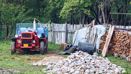 Rural scene of a backyard with tractor and wood pile Banco de Imagens - 137153213