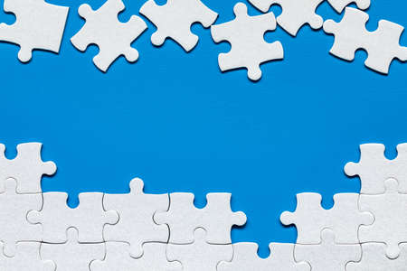 White jigsaw puzzle. White puzzle pieces on color background. Unfinished white jigsaw puzzle pieces on color background.  Stockfoto