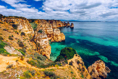 Panoramic view, Ponta da Piedade near Lagos in Algarve, Portugal. Cliff rocks and tourist boat on sea at Ponta da Piedade, Algarve region, Portugal. Ponta da Piedade, Algarve region, Portugal. Banco de Imagens - 137153261