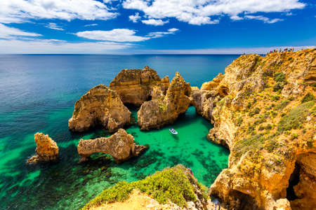 Panoramic view, Ponta da Piedade near Lagos in Algarve, Portugal. Cliff rocks and tourist boat on sea at Ponta da Piedade, Algarve region, Portugal. Ponta da Piedade, Algarve region, Portugal. Banco de Imagens - 137153272