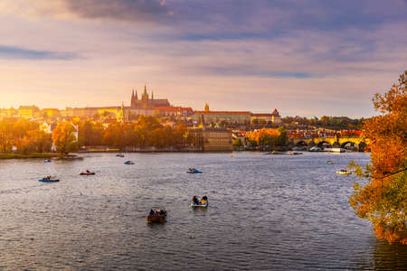 Prague Castle, Charles Bridge and boats on the Vltava river. View of Hradcany Prague Castle, Charles Bridge and a boats on the Vltava river in the capital of the Czechia. Boat cruise on Vltava river. Banco de Imagens - 137153317