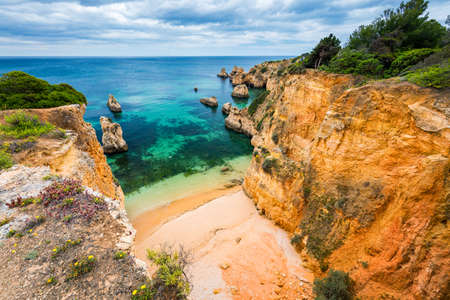 View of stunning beach with golden color rocks in Alvor town , Algarve, Portugal. View of cliff rocks on Alvor beach, Algarve region, Portugal. Banco de Imagens - 137153321