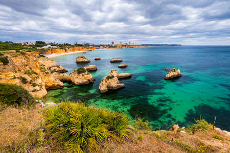 View of stunning beach with golden color rocks in Alvor town , Algarve, Portugal. View of cliff rocks on Alvor beach, Algarve region, Portugal. Banco de Imagens - 137153324