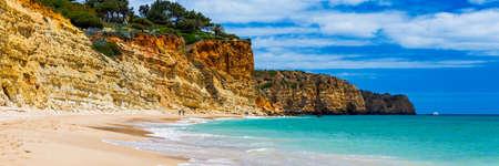 Praia de Porto de Mos in Lagos, Portugal. Praia do Porto de Mos, long beach in Lagos, Algarve region, Portugal. Beautiful golden beach, surrounded by impressive rock formations.  Stock fotó