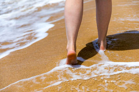 Woman walking barefoot on a beach. Close up leg of young woman walking along wave of sea water and sand on the summer beach. Travel Concept. Woman walking on sand beach leaving footprints in the sand.