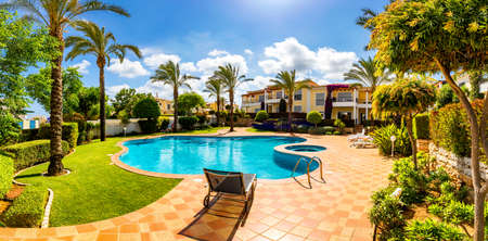 Swimming pool, sun-loungers and palm trees during a warm sunny day, paradise destination for vacations. Backyard swimming pool with garden full of palm trees and flowers. Backyard with swimming pool. Imagens - 137153489