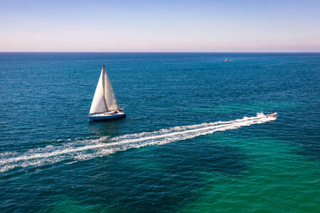 White sail boat isolated in blue sea water. Sailboat in the sea in the sunlight, luxury summer adventure, active vacation in Mediterranean sea. Yacht sailing on opened sea. Sailing boat. Imagens - 137153768