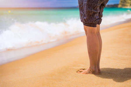 Closeup on leg of young woman standing on sea shore. Woman legs and feet walking on the sand of the beach with the sea water in the background. Woman standing on the beach with wave sea. Imagens - 137153703