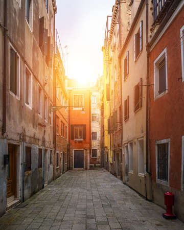 Street in Venice, Italy. Narrow street among old colorful brick houses in Venice, Italy. Venice postcard Banque d'images - 138376761