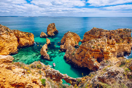 Panoramic view, Ponta da Piedade near Lagos in Algarve, Portugal. Cliff rocks and tourist boat on sea at Ponta da Piedade, Algarve region, Portugal. Ponta da Piedade, Algarve region, Portugal. Banque d'images - 138376874
