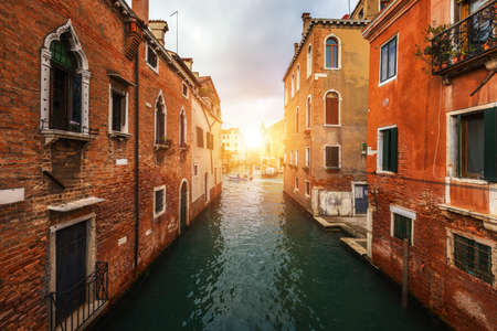 View of the street canal in Venice, Italy. Colorful facades of old Venice houses. Venice is a popular tourist destination of Europe. Venice, Italy. Banque d'images - 138377248