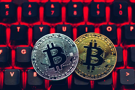 Bitcoin on compuer keyboard in background, symbol of electronic virtual money and mining cryptocurrency concept. Coin crypto currency bitcoin lies on the keyboard. Bitcoin on keyboard. Banque d'images - 138377332