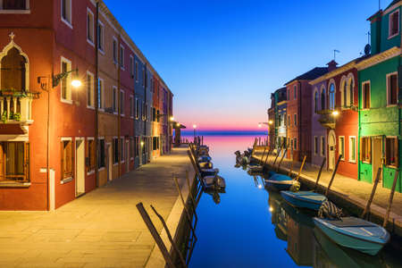 Street view with colorful buildings in Burano island at night, Venice, Italy. Architecture and landmarks of Burano, Venice postcard. Scenic canal and colorful architecture in Burano island near Venice, Italy Banque d'images - 138377343