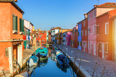 Street with colorful buildings in Burano island, Venice, Italy. Architecture and landmarks of Burano, Venice postcard. Scenic canal and colorful architecture in Burano island near Venice, Italy Banque d'images - 138377384
