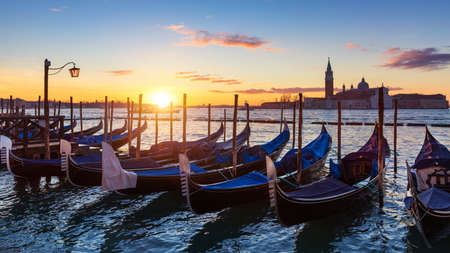 Venice with famous gondolas at sunrise, Italy. Gondolas in lagoon of Venice on sunrise, Italy. Venice with gondolas on Grand Canal against San Giorgio Maggiore church. Banque d'images - 138377386