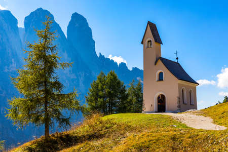 Chapel of San Maurizio at Passo Gardena, South Tyrol, Italy.  View to path to small white chapel San Maurizio and Dolomiti mountain. San Maurizio chapel on the Gardena Pass, South Tyrol, Italy. Banque d'images - 138377387