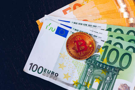 Golden bitcoin over Euro money. Bitcoin cryptocurrency. Crypto currency concept. Bitcoin with euro bills. Bitcoins stacked on euro banknotes. Banque d'images - 138377458