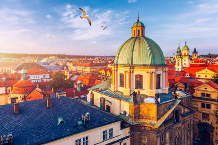 Aerial panorama view with flying birds of the Old Town in Prague, Czech Republic. Red roof tiles panorama of Prague old town.  Prague Old Town Square houses with traditional red roofs. Czechia.