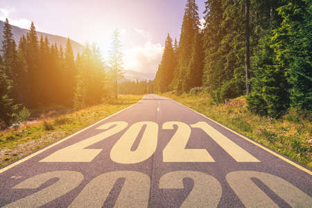 Empty asphalt road and New year 2021 concept. Driving on an empty road in the mountains to upcoming 2021 and leaving behind old 2020. Concept for success and passing time.