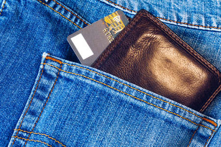 Credit card in wallet in pocket of jeans, closeup. Closeup of wallet and credit card in jeans trousers pocket.