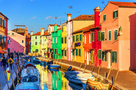 Street with colorful buildings in Burano island, Venice, Italy. Architecture and landmarks of Burano, Venice postcard. Scenic canal and colorful architecture in Burano island near Venice, Italy Imagens