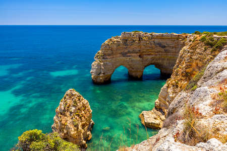 Natural caves at Marinha beach, Algarve Portugal. Rock cliff arches on Marinha beach and turquoise sea water on coast of Portugal in Algarve region. Banque d'images - 138378221
