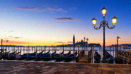 Scenic view of San Giorgio Maggiore, gondolas and lamp at colorful sunrise, Venice, Italy. Sunset in Venice. Gondolas at Saint Marks Square and church of San Giorgio Maggiore on background, Italy, Europe
