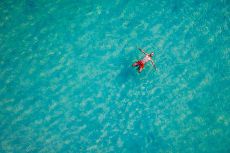 Drone view of a man floating in tropical sea water. Aerial view of young man floating on sea water enjoying sunbathing and vacations in tropical destination. People travel tourism holidays concept.