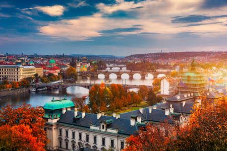 Autumn view to Charles bridge on Vltava river in Prague, Czech Republic. Autumn view to Charles Bridge, Prague old town and Vltava river. Czechia. Scenic autumn view of the Old Town with red foliage. 스톡 콘텐츠