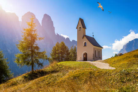 Chapel of San Maurizio at Passo Gardena, South Tyrol, Italy. View to path to small white chapel San Maurizio and Dolomiti mountain. San Maurizio chapel on the Gardena Pass, South Tyrol, Italy. Stock Photo