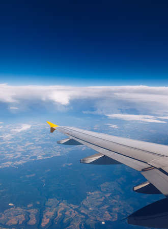 View of the wing of an airplane flying above the clouds at high altitude under a blue sky from the passenger window. In flight over Europe. View of jet airplane wing flying in blue sky over clouds. Standard-Bild - 142068623