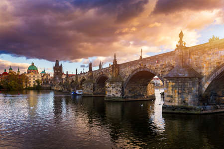 Autumn view to Charles bridge on Vltava river in Prague, Czech Republic. Autumn view to Charles Bridge, Prague old town and Vltava river. Czechia. Scenic autumn view of the Old Town with red foliage. Banque d'images - 142093726