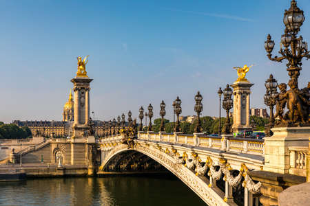 Pont Alexandre III bridge over river Seine in the sunny summer morning. Bridge decorated with ornate Art Nouveau lamps and sculptures. The Alexander III Bridge across Seine river in Paris, France. Standard-Bild - 142093770