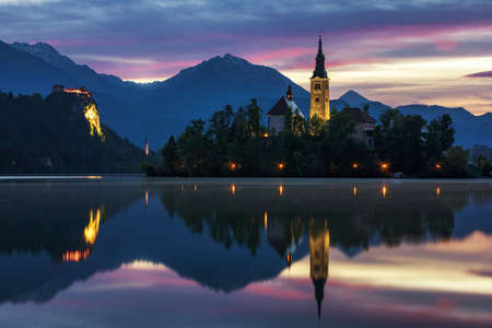 Dramatic sunrise on lake Bled, sunrise view on Bled lake, island, Pilgrimage Church of the Assumption of Maria and Castle with mountain range (Stol, Vrtaca, Begunjscica). Bled, Slovenia, Standard-Bild - 142093771