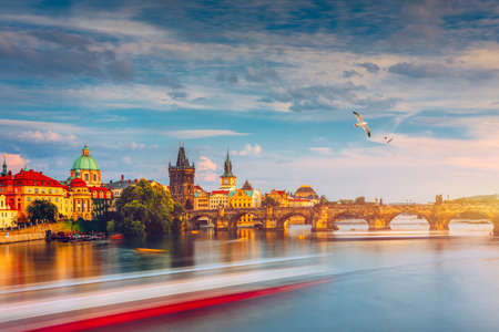Prague Castle, Charles Bridge and boats on the Vltava river. View of Hradcany Prague Castle, Charles Bridge and a boats on the Vltava river in the capital of the Czechia. Boat cruise on Vltava river. Banque d'images - 142093826